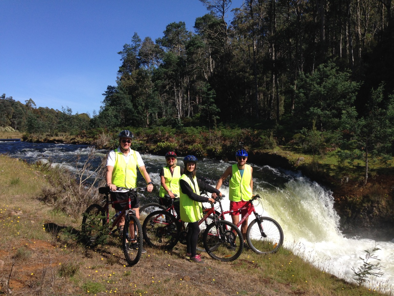 bicyclists near a waterfall